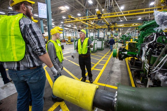 "Glen Snyder, a retired Deere worker, leads the Van Regenmorter family from Sioux Center as they take the ""gold key tour"" at the Waterloo assembly plant Tuesday, April 9, 2019."
