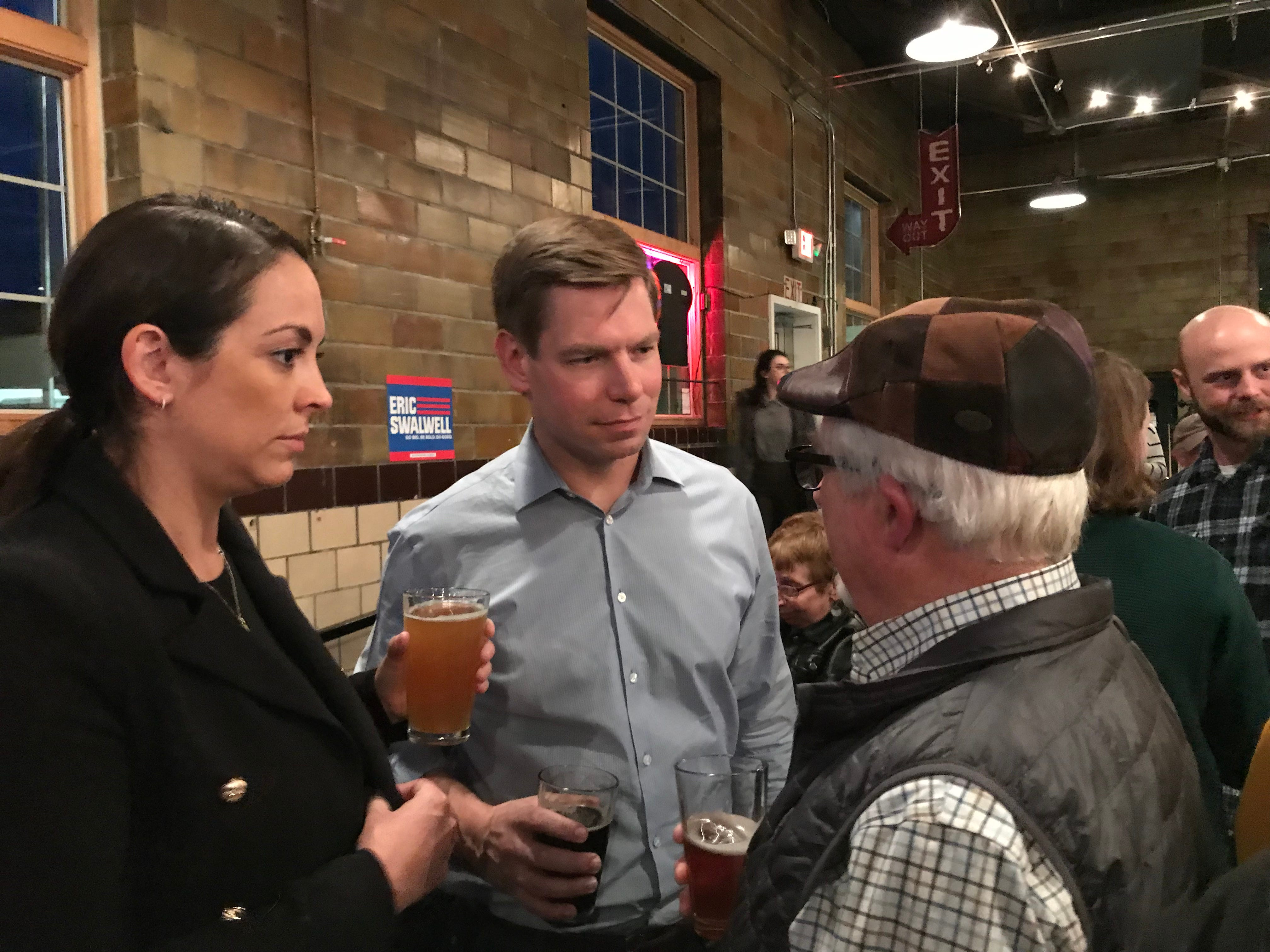 Eric Swalwell, middle, and his wife, Brittany, speak with John Klaus of Ames at Torrent Brewing in Ames Thursday night. Swalwell stopped in Ames for his first visit in Iowa since announcing his 2020 candidacy.