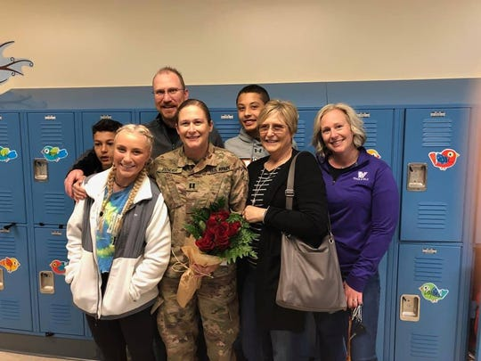 Iowa National Guard Capt. Keri Pender, center  uniform, surrounded by her family after surprising her children