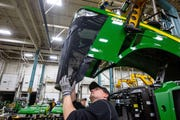Workers assemble a tractor at John Deere's Waterloo assembly plant Tuesday, April 9, 2019.