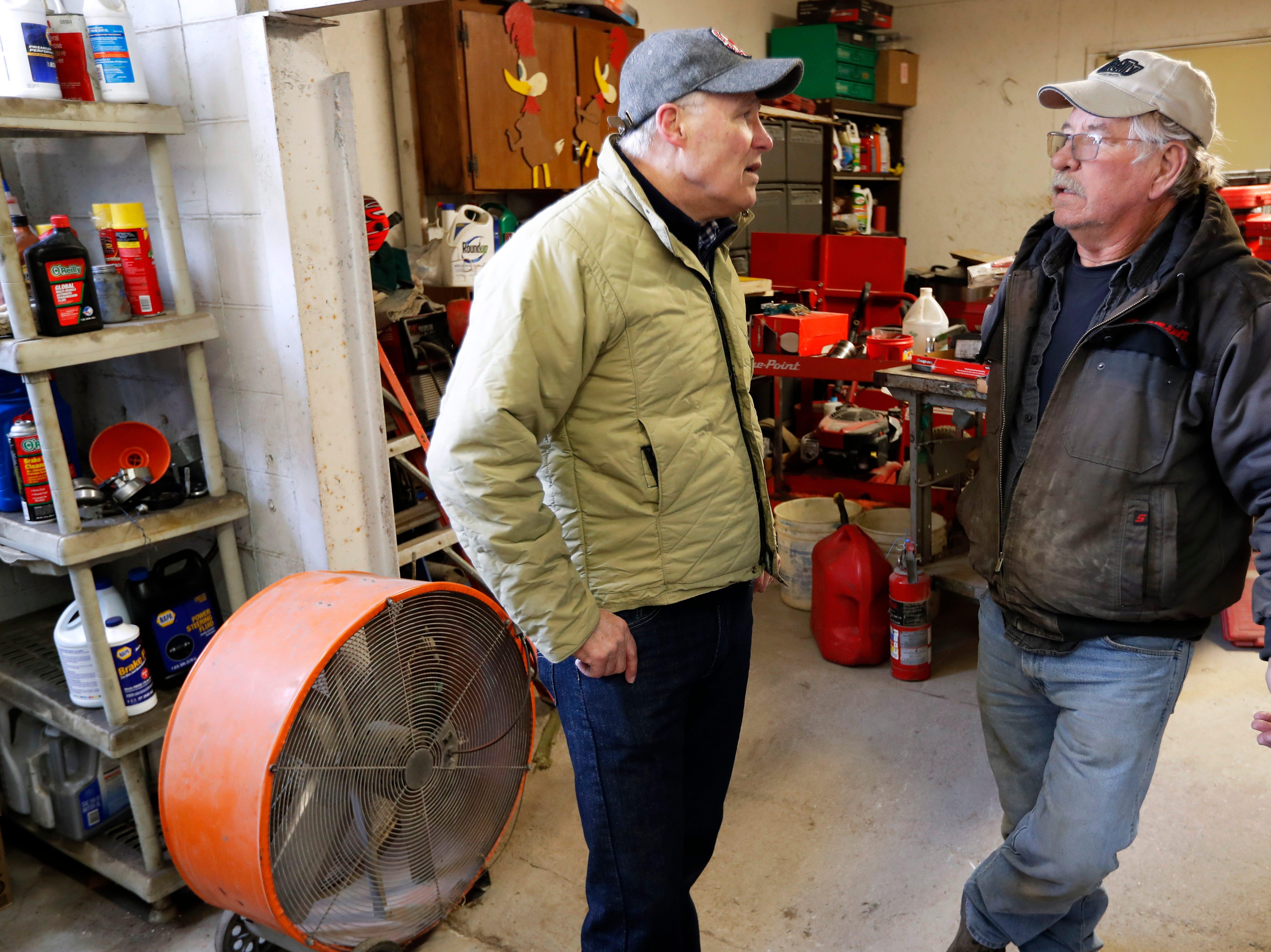 2020 Democratic presidential candidate Washington Gov. Jay Inslee talks with Ron Perry, of Hamburg, Iowa, right, while touring flood damage, Friday, April 12, 2019, in Hamburg, Iowa.