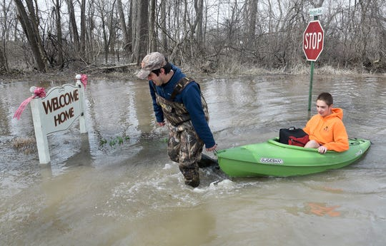 Louis Flory gets his younger brother Levi Flory, a ninth grader at Monroe Middle College at MCCC, after school Thursday, April 11, 2019, using a canoe to take him home in North Shores, LaSalle, Mich. The water was not even over the road when Levi went to school Thursday morning.