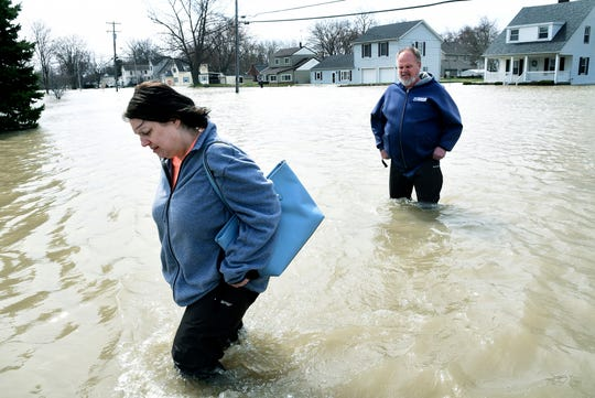 Disappointed, Sherry Stanley holds her waders up as she walks to her home with her fiance Ken Williams in North Shores in LaSalle, Mich., Thursday, April 11, 2019. The couple had just moved into their home two months ago. (Tom Hawley/The Monroe News via AP)