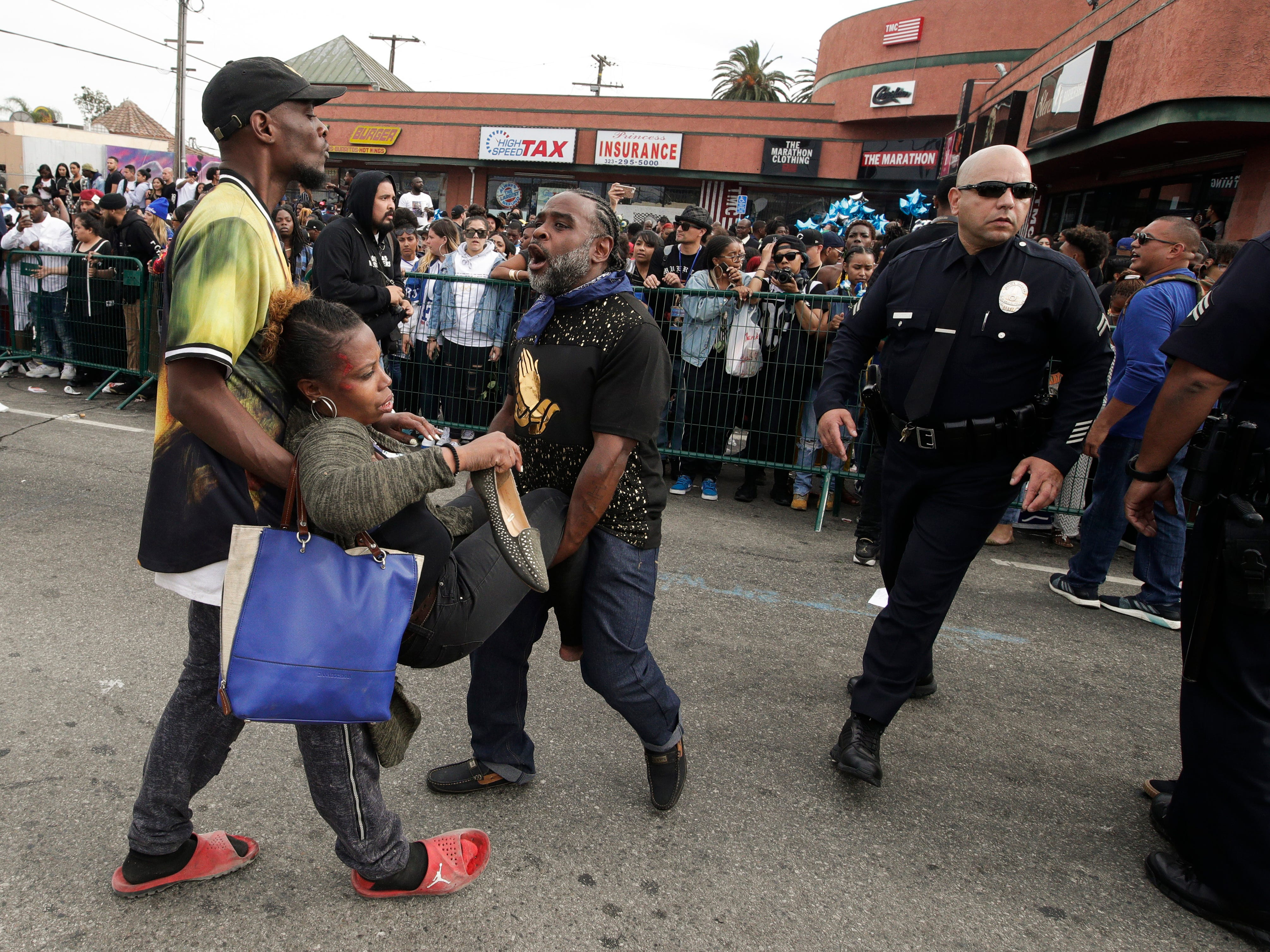 Two men carry a woman injured in a stampede as people gather to watch a hearse carrying the casket of slain rapper Nipsey Hussle Thursday, April 11, 2019, in Los Angeles. The 25-mile procession traveled through the streets of South Los Angeles after a memorial service, including a trip past Hussle's clothing store, The Marathon, rear, where he was gunned down March 31.