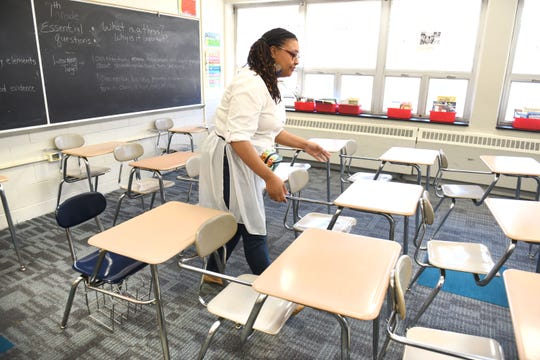 Palmer Park Preparatory Academy teacher Shauntay Frazier adjusts the desks in her classroom.