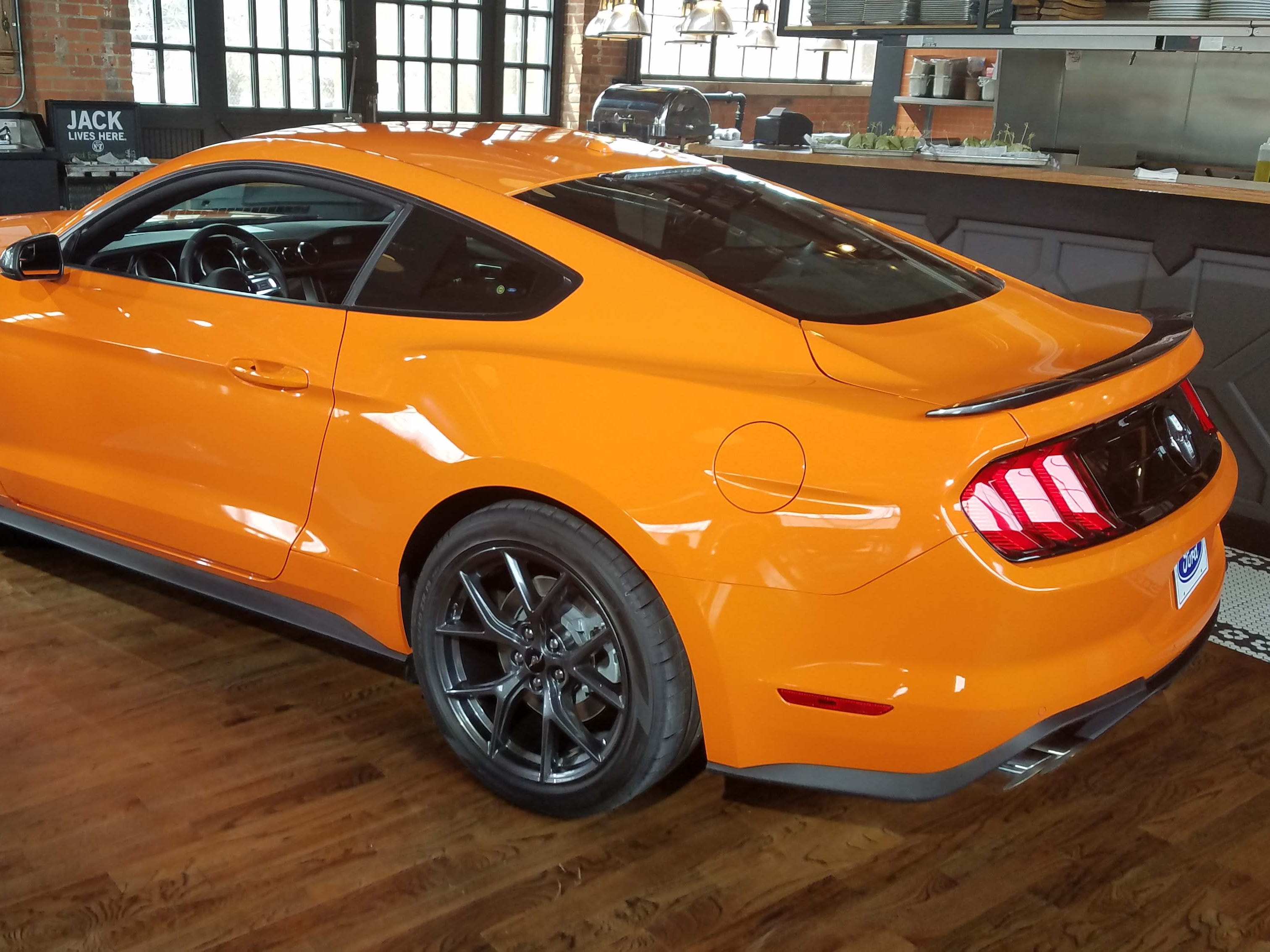 The fastback of the Ford Mustang Ecoboost High Performance is completed with a black spoiler to match its black, 19-inch wheels and gray mirrors.