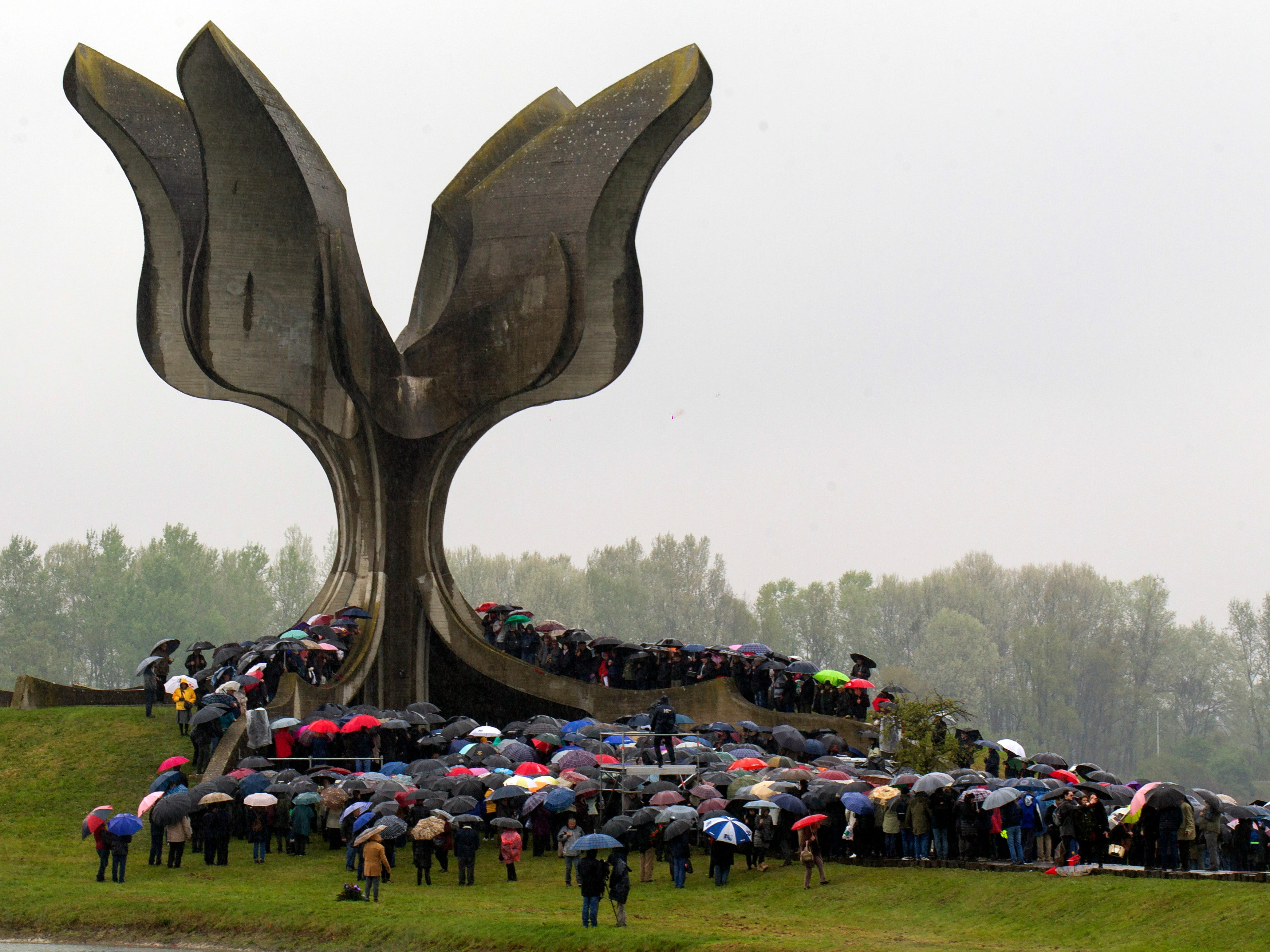 Hundreds gather at the memorial center to pay their respects for tens of thousands of people killed in death camps run by Croatia's pro-Nazi puppet state in WWII, in Jasenovac, Croatia, Friday, April 12, 2019.  Croatia's Jewish, Serb, anti-fascist and Roma groups have commemorated the victims of a World War II death camp by snubbing the official ceremonies for the fourth year in a row over what they say is government inaction to curb neo-Nazi sentiments in the European Union country.
