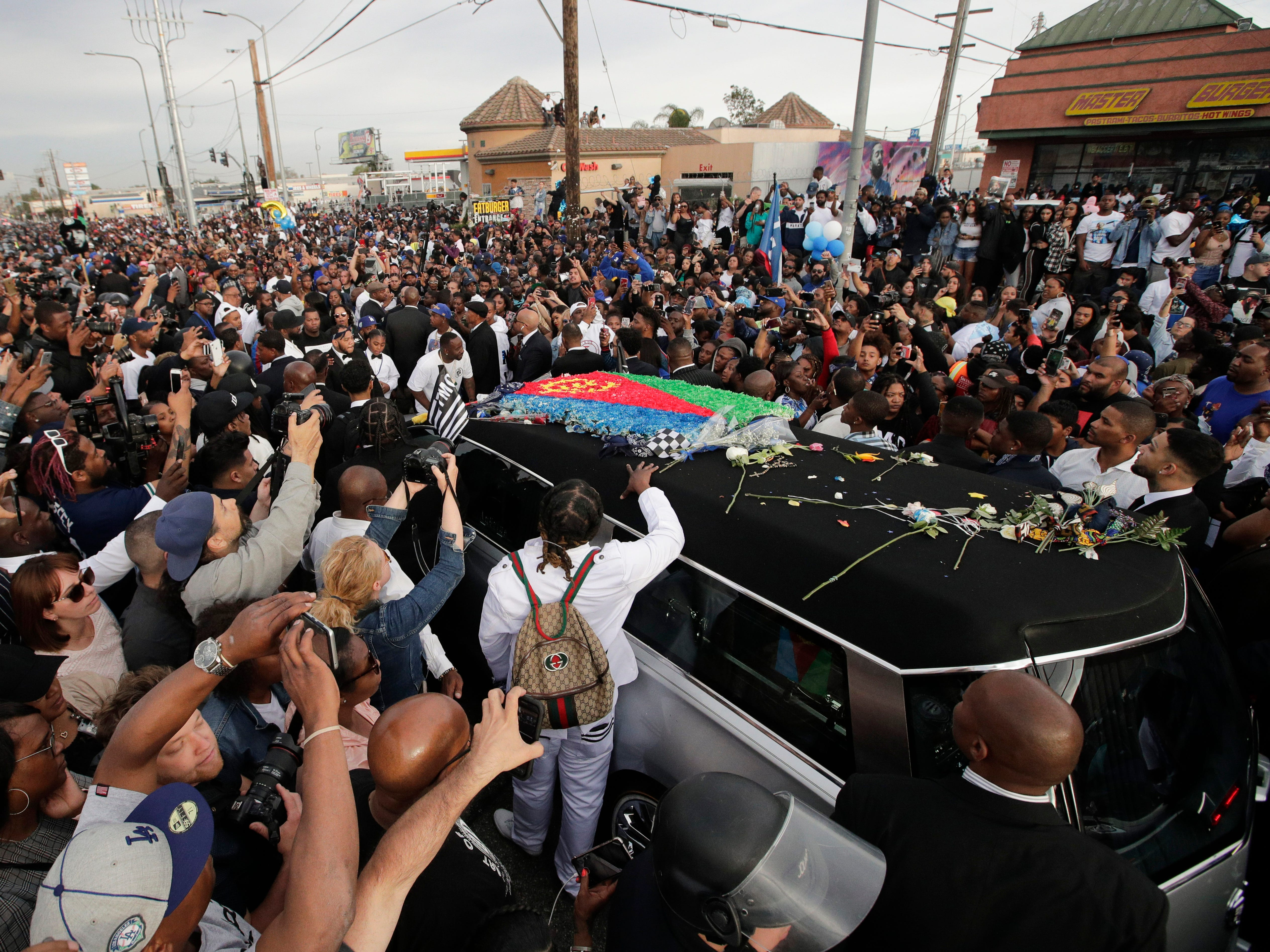 A hearse carrying the casket of slain rapper Nipsey Hussle, draped in the flag of his father's native country, Eritrea in East Africa, passes through the crowd Thursday, April 11, 2019, in Los Angeles. Hussle was shot to death March 31 while standing outside The Marathon, his South Los Angeles clothing store, not far from where the rapper grew up.