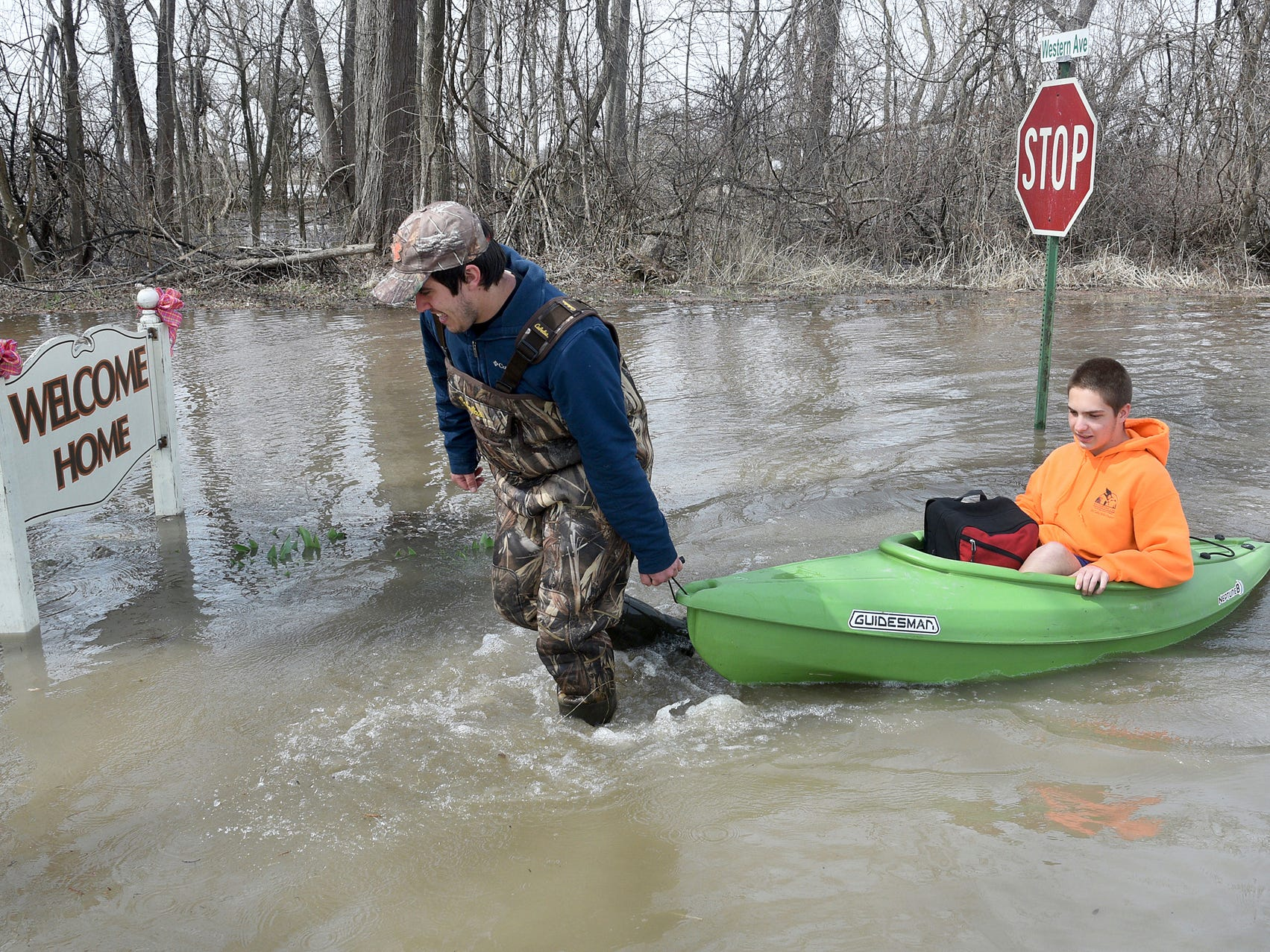 Louis Flory gets his younger brother Levi Flory, a ninth grader at Monroe Middle College at MCCC, after school Thursday, April 11, 2019 using a kayak to take him home in North Shores, LaSalle, Mich. (The water was not over the road when Levi went to school Thursday morning. )
