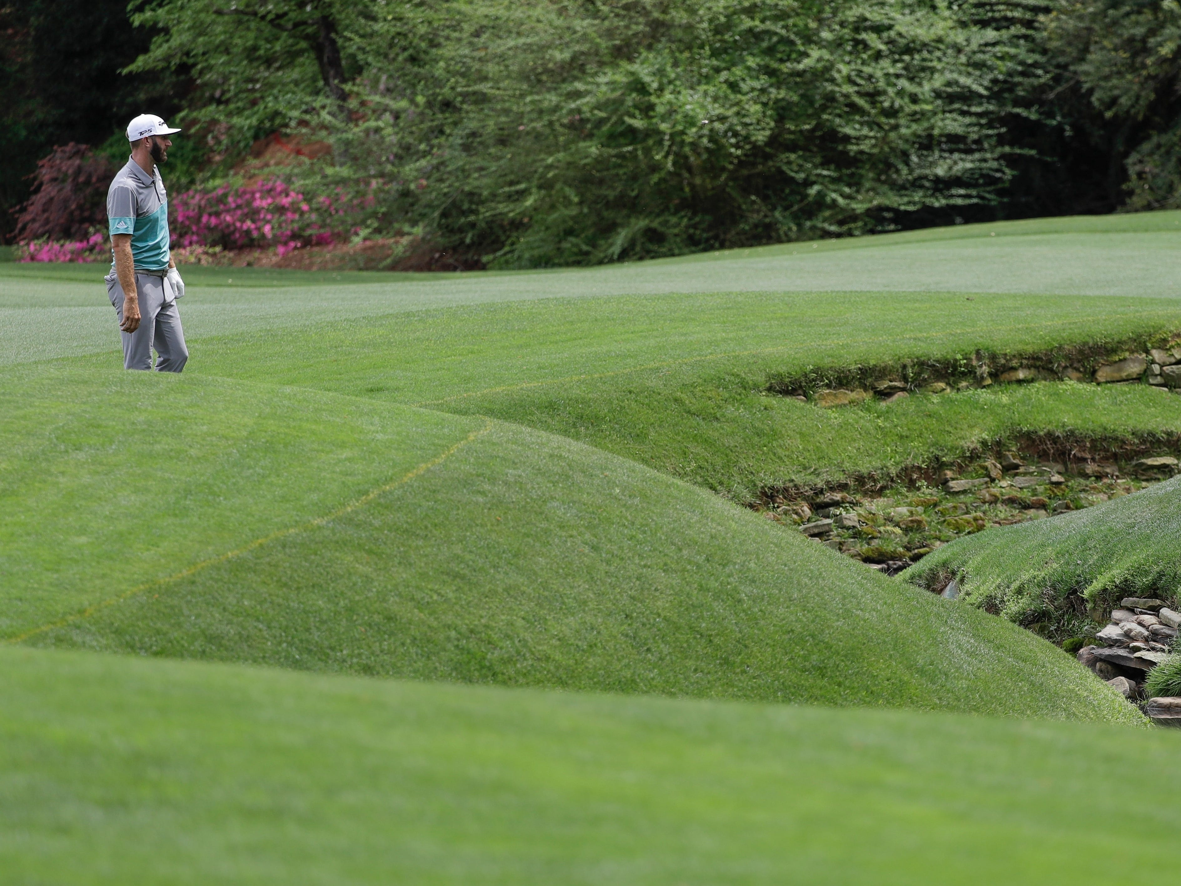Dustin Johnson looks over Rae's creek at the 13th green during the second round for the Masters golf tournament Friday, April 12, 2019, in Augusta, Ga.
