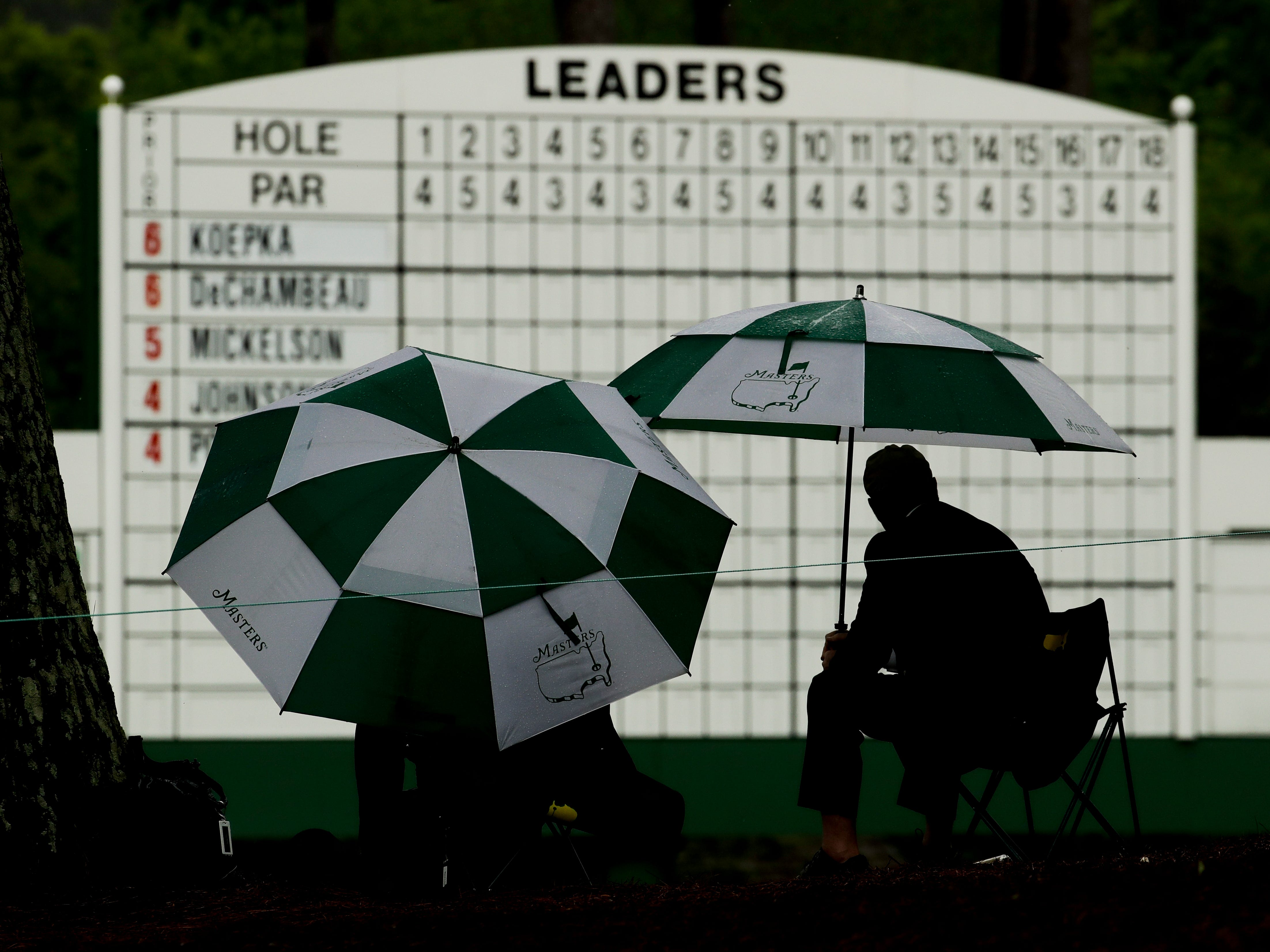 Patrons watch from under umbrellas during the second round for the Masters golf tournament Friday, April 12, 2019, in Augusta, Ga.