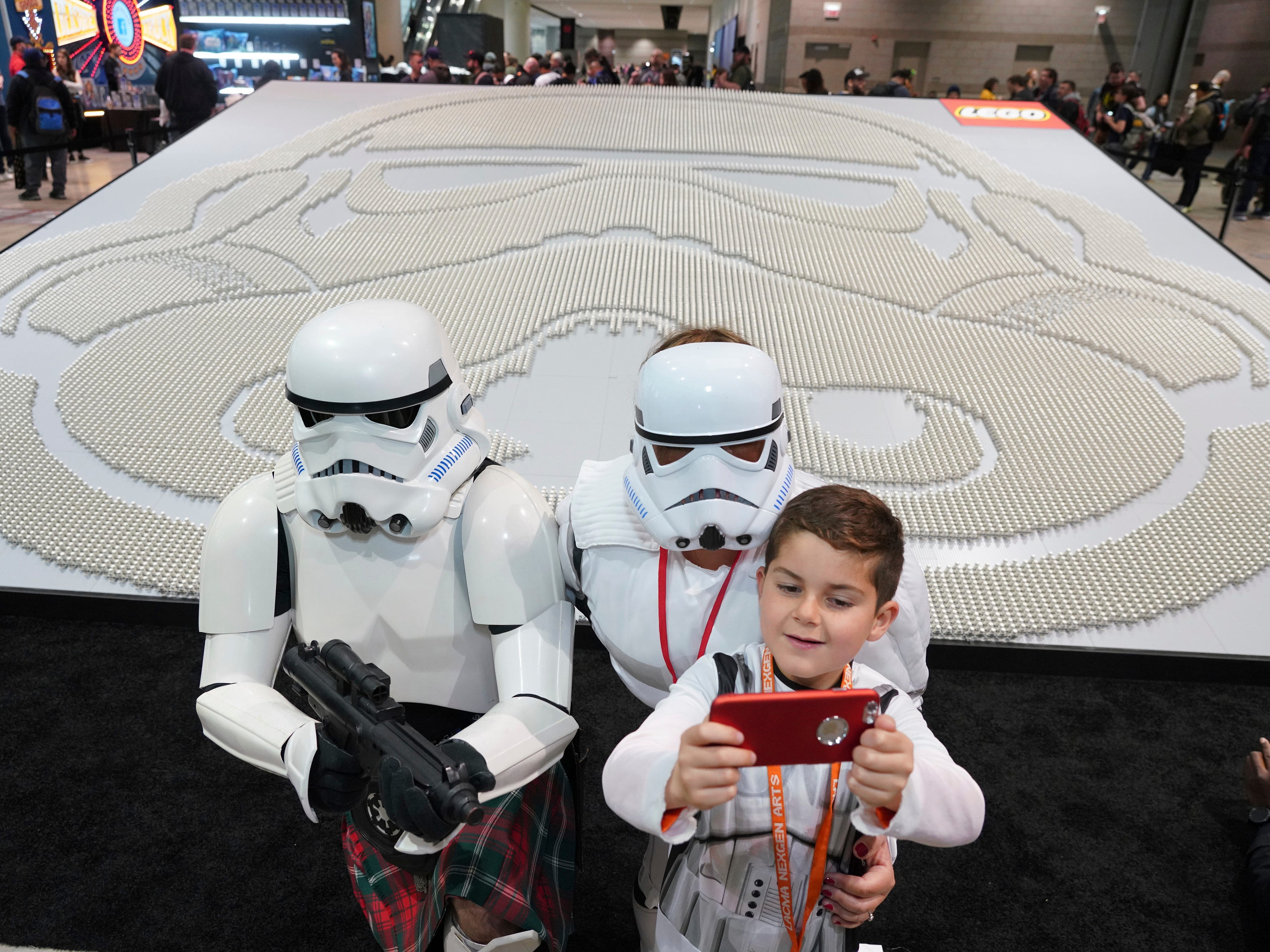 Star Warsenthusiast Joseph Naiman, 7, takes a selfie with his parents Marshall, left, and Danelle next to thelargestdisplay ofLEGOStar Warsmini figures.