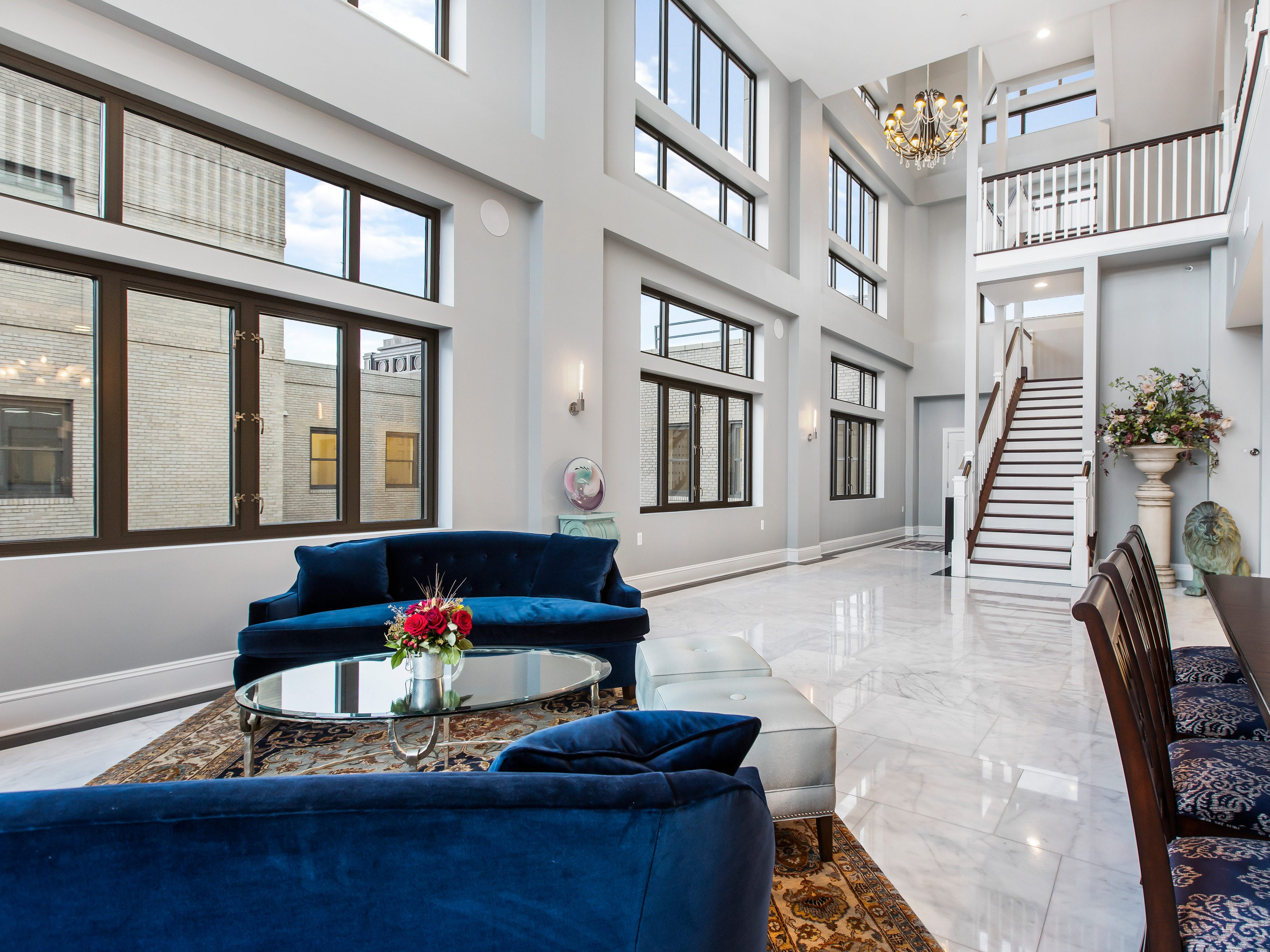 The foyer is 3 stories high an opens under soaring ceilings and walls of windows featuring stunning views of the Detroit skyline and the Detroit River.