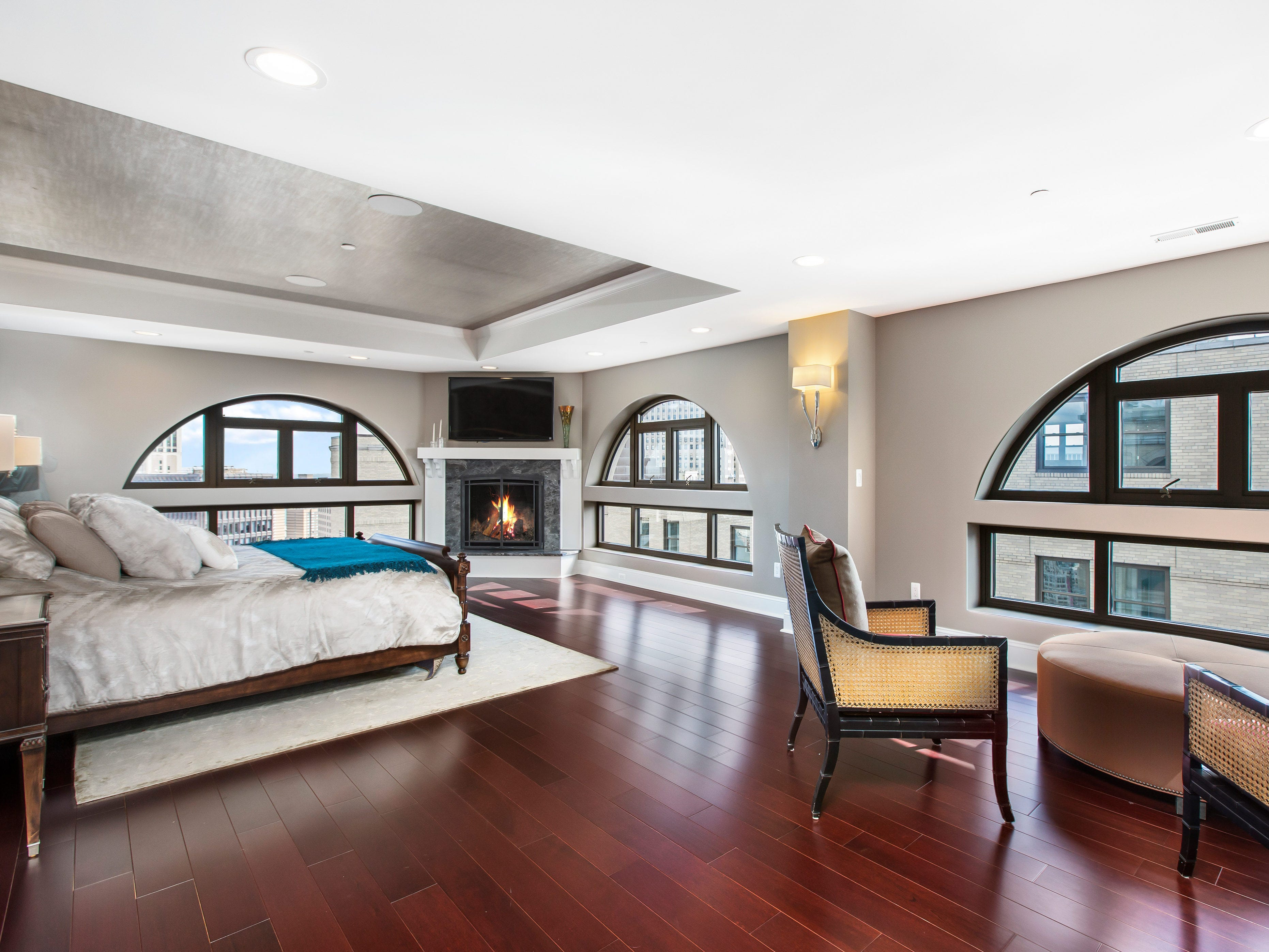 There is a fireplace and sitting area in this bedroom.