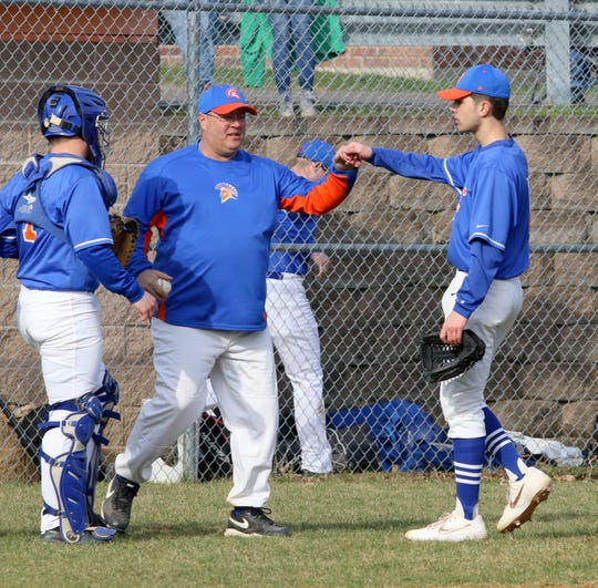 Thomas A. Edison head coach Mike Bennett congratulates pitcher Xander Burch at the end of the inning April 11, 2019 against Lansing in Elmira Heights.