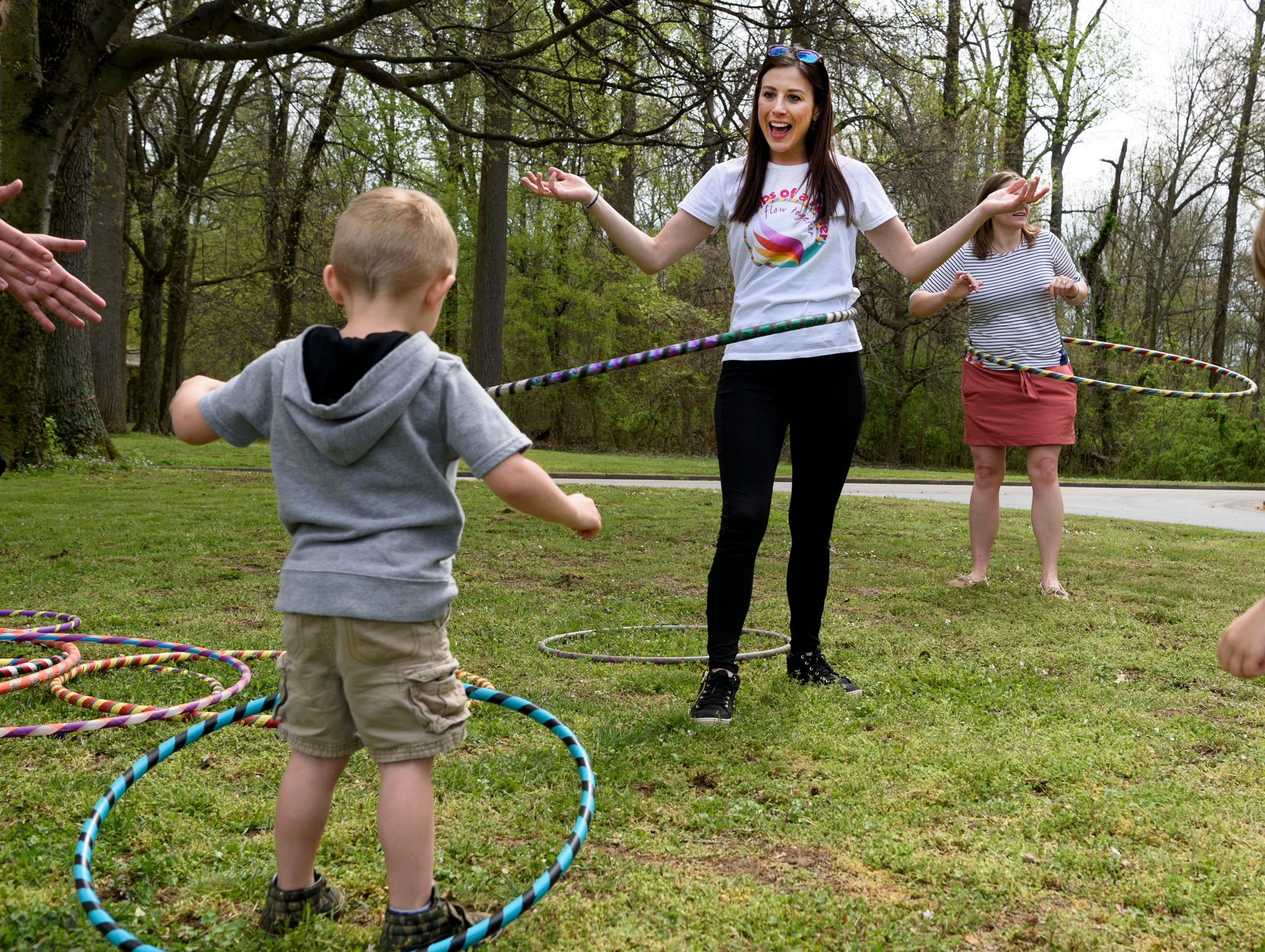 Abbi Killebrew, center, known as Absmarie, shows three-year-old Jeremiah Stewart, left, how to use a hula hoop during the CAPE's annual Family Fun Day at Wesselman Park in Evansville, Ind., Friday, April 12, 2019.