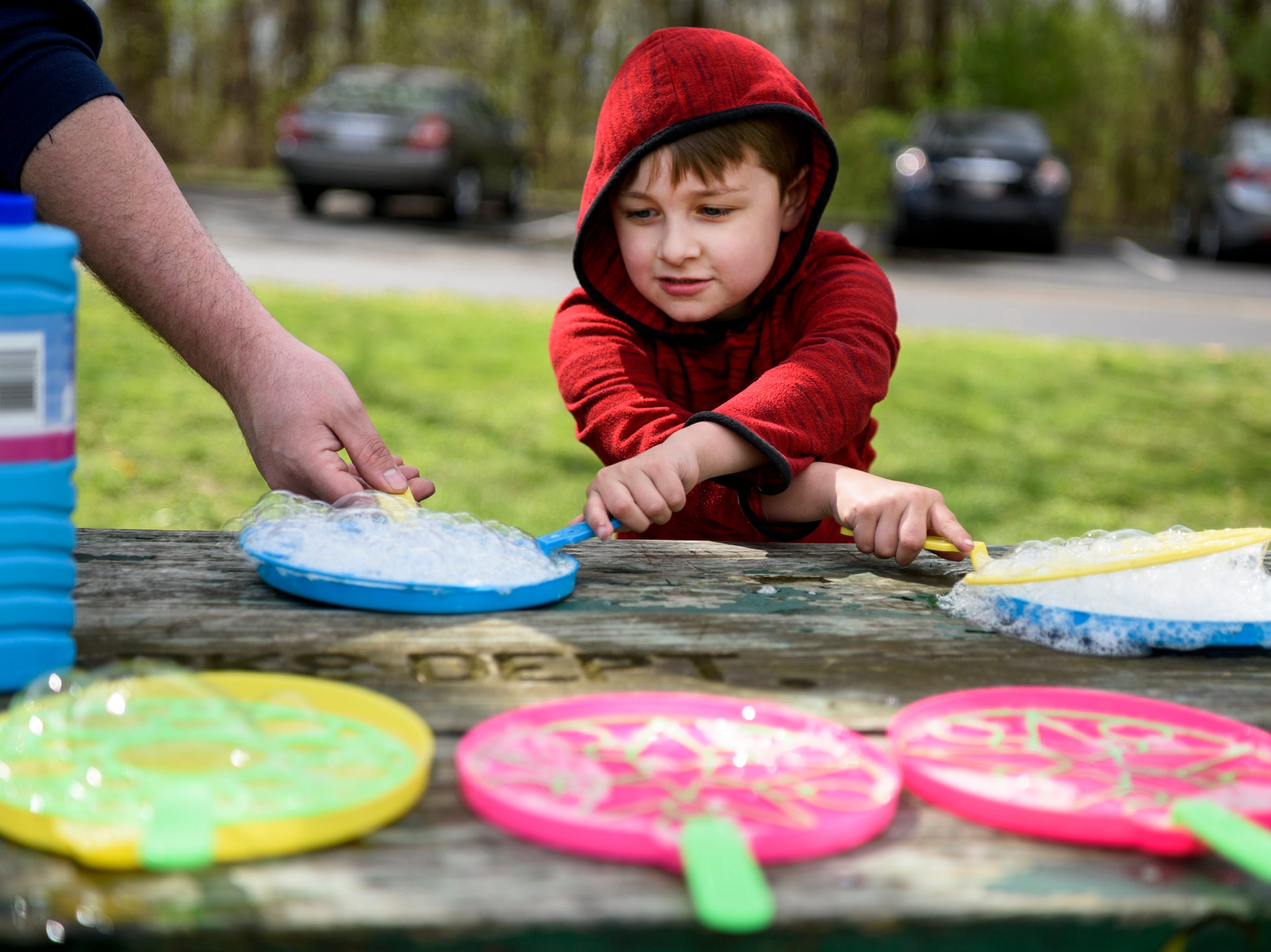 Jaxton Mason, 5, center, and his father Zachary Mason, left, play with bubbles during the local Community Action Program of Evansville & Vanderburgh County's (CAPE) annual end of the year Family Fun Day at Wesselman Park in Evansville, Ind., Friday, April 12, 2019.