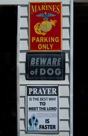Signs on the garage of David and Patricia Goodwin of Jimtown offer warnings to any potential trespassers.