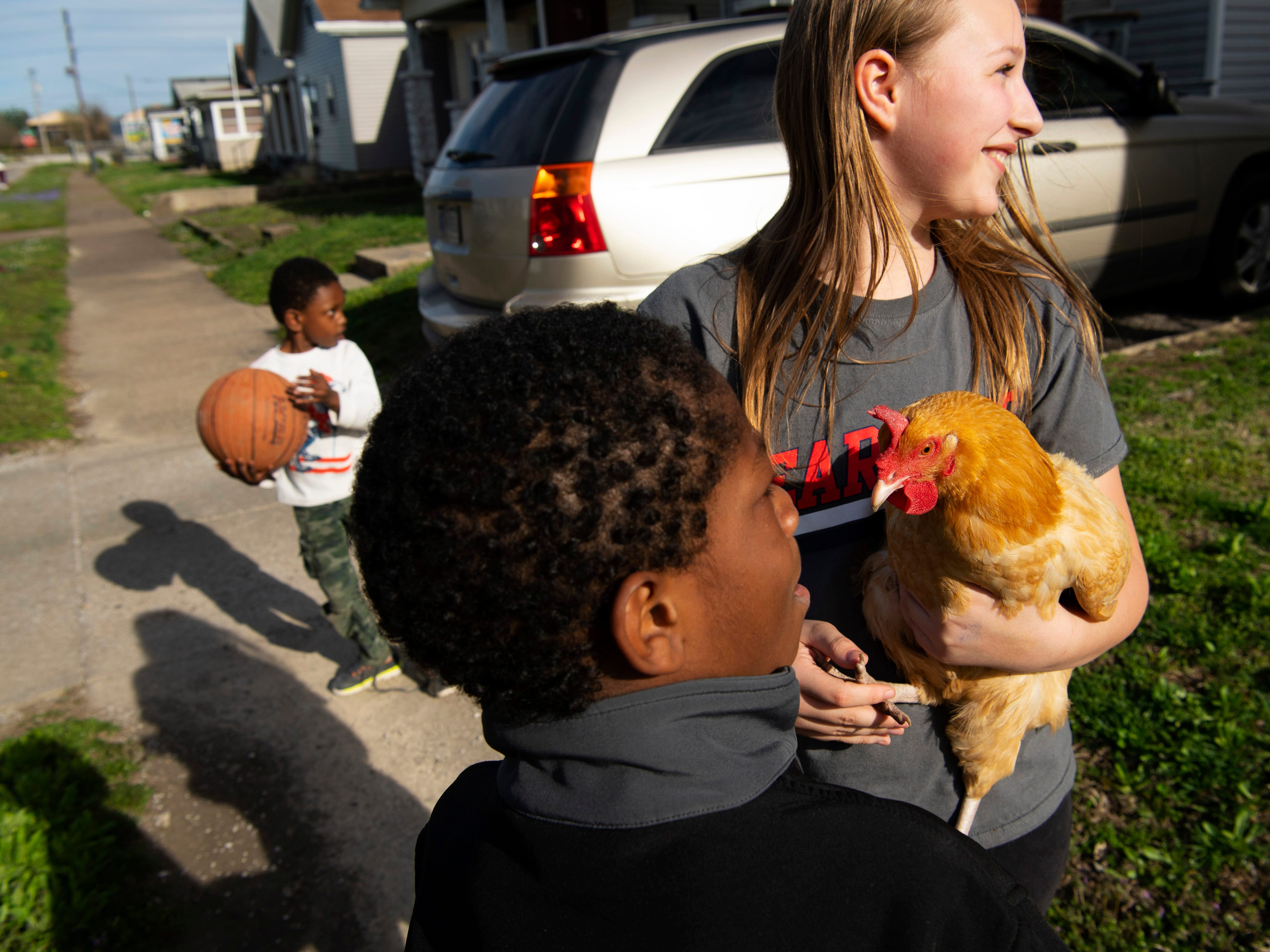 The Jimtown neighborhood is teeming with children and sometimes their pets, like Bailey Post, 12, and her chicken Tuesday evening. Brothers Jave'andre Burton, 8, front, and Treyveon Burton, 4, were also enjoying the sunny afternoon.