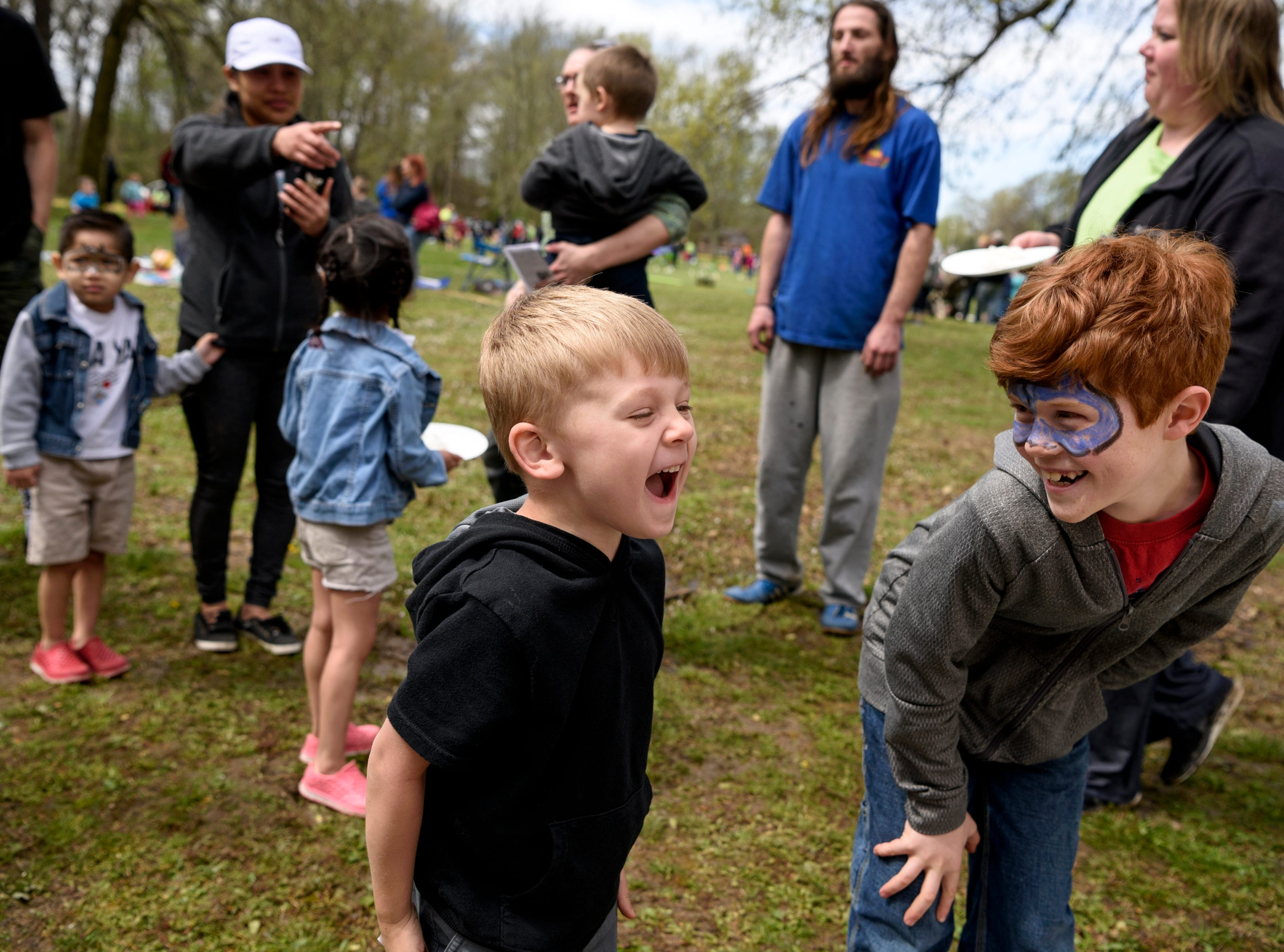Theo Stewart reacts to throwing a plate of whipped cream in Billie Walker's face, not pictured, with the help of Walker's son Alton Deig, 10, right, during the annual Family Fun Day for the Community Action Program of Evansville & Vanderburgh County, Inc. (CAPE) at Wesselman Park in Evansville, Ind., Friday, April 12, 2019. CAPE employees, like Walker, volunteered to have whipped cream smushed into their faces to raise money for the organization.
