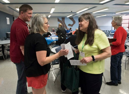 Connie Whitman, right, hands a campaign flyer to Mindy Moats during the Plaza Park Neighborhood Association meeting Thursday, April 11, 2019. Whitman is an Independent, running as a Republican, against Evansville Mayor Lloyd Winnecke.