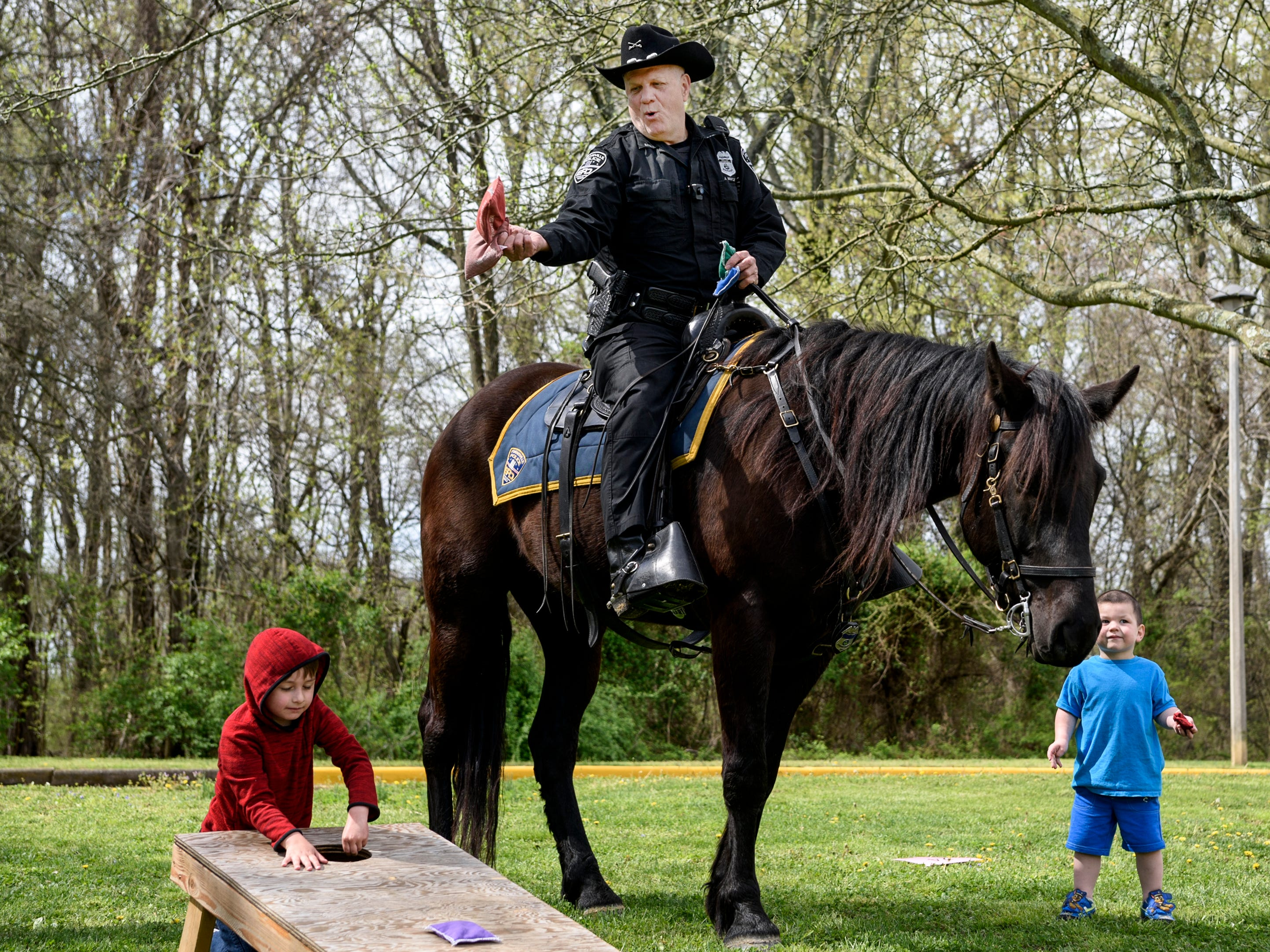 Evansville Police Officer Jeff Vantlin plays corn hole as he sits on top of Speck, an EPD police horse, as Jaxton Mason, left, and Jesse Vaughn, right, collect bean bags to give to Vantlin during CAPE's annual Family Fun Day at Wesselman Park in Evansville, Ind., Friday, April 12, 2019.