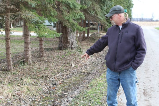 Jed Vollmar points to a ditch where raw sewage is dumped by neighbors along County Road 259 at Wightman's Grove.