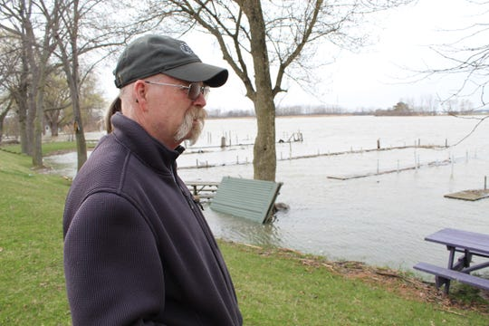 Jed Vollmar, a lifetime resident of Wightman's Grove, stands on top of the grove's dike that separates about 85 homes from the Sandusky River.