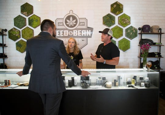 Natasha Lehtola, center, and Cole Peacock help a customer at Seed and Bean Market recently in downtown Fort Myers. The new shop specializes in coffees and teas infused with CBD, a calming and non-psychoactive compound found in marijuana.