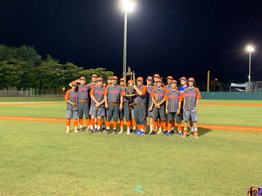 The Cape Coral baseball team poses for pictures with the championship trophy following their 10-7 victory over Riverdale on Thursday night.