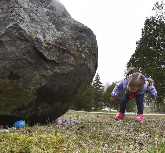 Lily Baudhuin of Germantown finds eggs under a rock during a past Easter egg hunt at Fitzgerald Park in Ellison Bay.