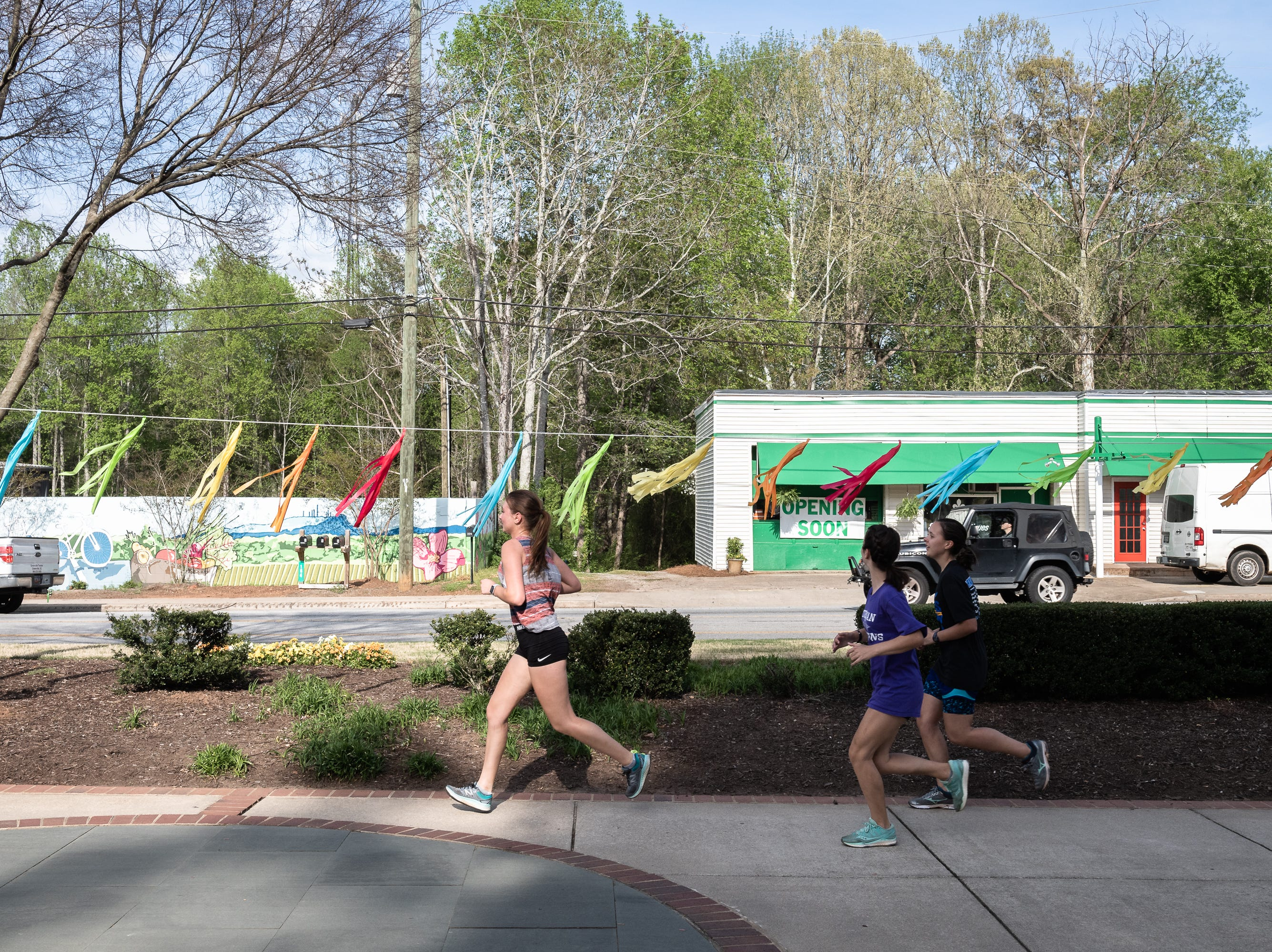 Runners on the Swamp Rabbit Trail on South Main Street in Travelers Rest Apr. 11, 2019.