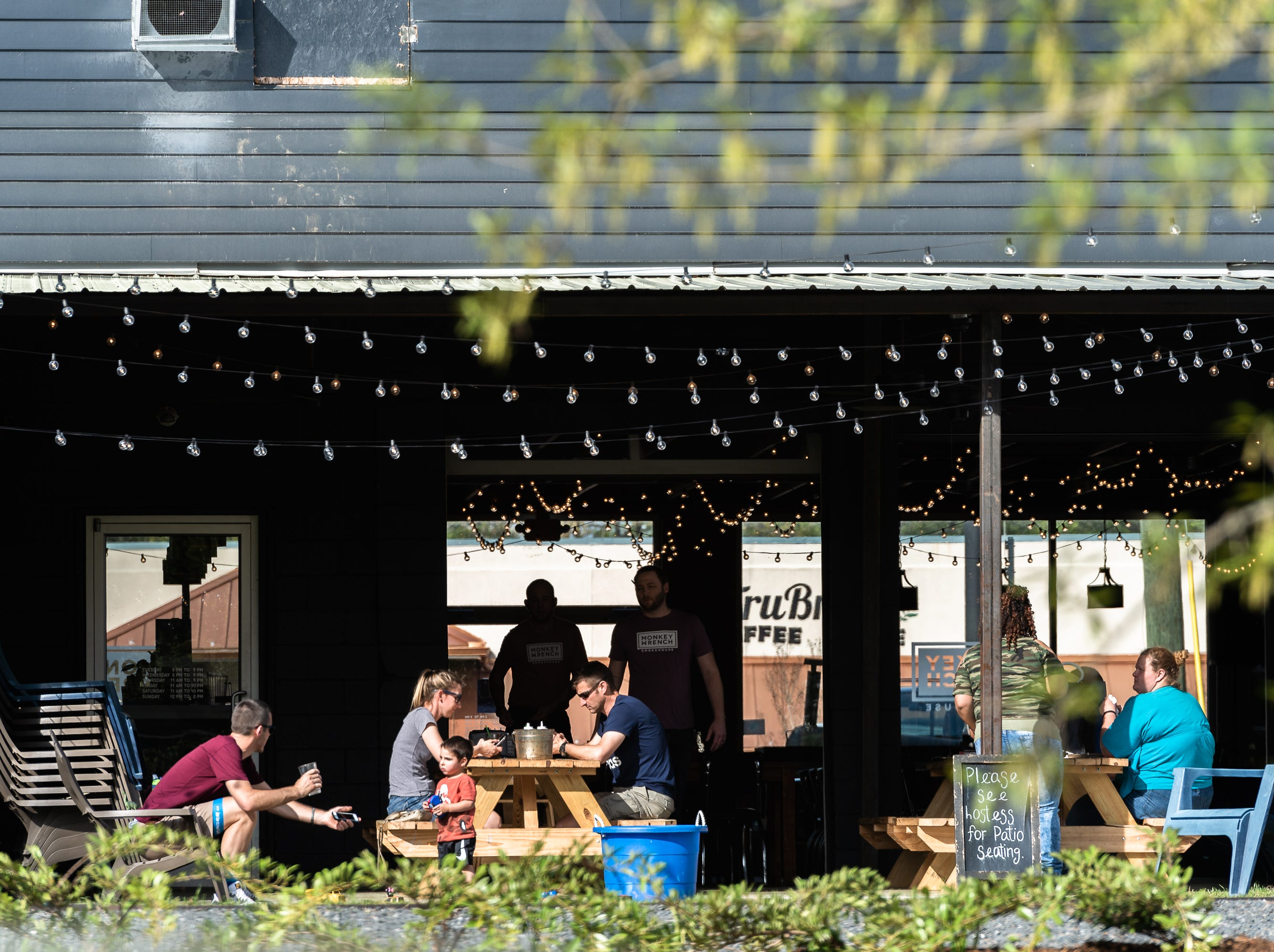 Patrons sit at an outdoor patio at Monkey Wrench Smokehouse in Travelers Rest, Apr. 11, 2019.