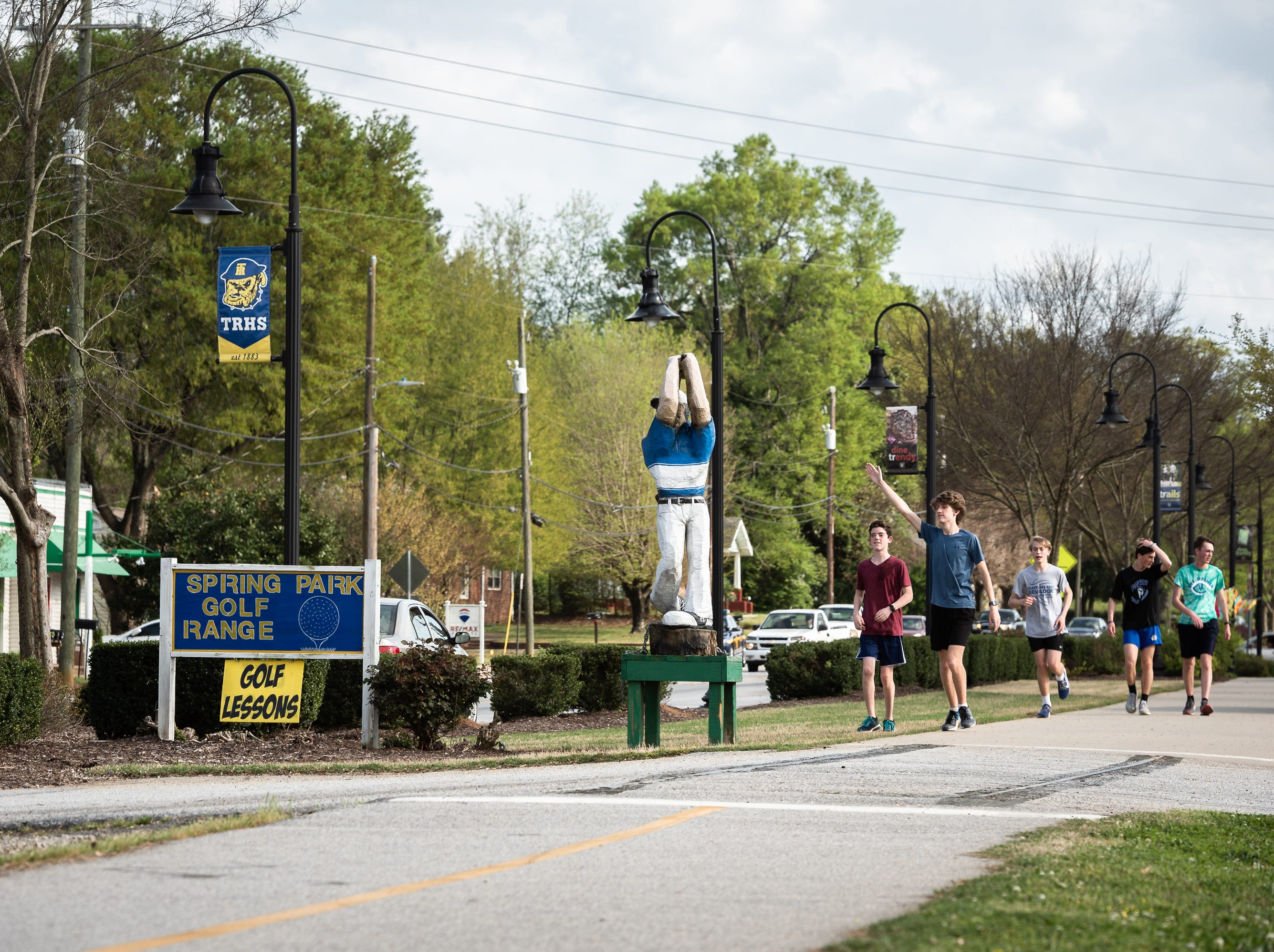 Runners from Travelers Rest High School run down the Swamp Rabbit Trail on South Main Street in Travelers Rest Apr. 11, 2019.