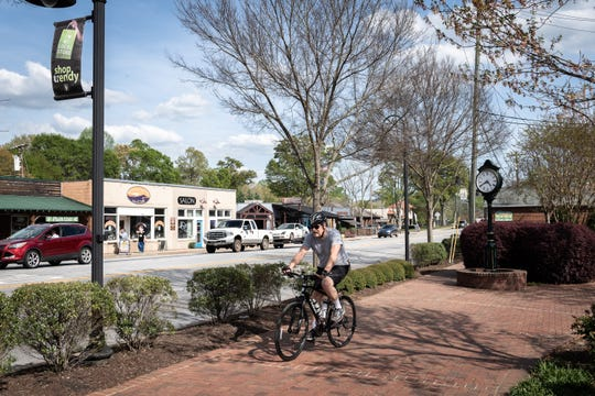 A cyclist travels down the Swamp Rabbit Trail on South Main Street in Travelers Rest Apr. 11, 2019.