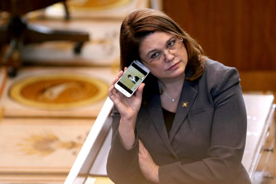 FILE - In this March 3, 2016, file photo, Oregon state Sen. Sara Gelser listens to a live stream as members of the House of Representatives finish business before adjourning the 2016 legislative session at the Oregon State Capitol in Salem, Ore. Oregon lawmakers including Gelser are demanding answers from the state's child welfare agency after a report that a 9-year-old girl in foster care was sent to a Montana facility for six months and injected with Benadryl to control her behavior. A legislative hearing Thursday, April 11, 2019 largely focused on the news report this week by Oregon Public Broadcasting that also revealed caseworkers didn't visit the girl for months. (Anna Reed/Statesman-Journal via AP, File)