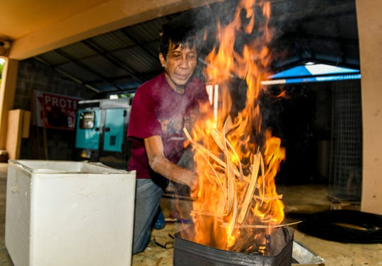 In this file photo, maintenance worker Santiago Bagana Jr. adds dried palm fronds to a fire blazing in a metal can behind the office of the St. Anthony - St. Victor Catholic Church, in Tamuning. The ashes from the leaves will be used for Ash Wednesday.