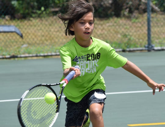 Leah San Agustin rushes to return the ball during her U10 division match in the Youth Singles Division of the 47th Annual Chamorro Open.