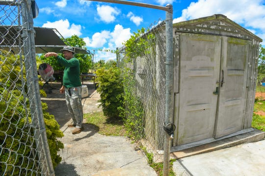 Lease holder Robert Celestial stands next to an old plastic-molded storage shed his family once used as a shower room, as he self-constructed a concrete home on a two-acre lot granted to him for use by the CHamoru Land Trust Commission, during a compliance inspection visit on Wednesday, April 10, 2019.