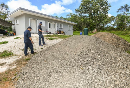 CHamoru Land Trust Commission Administrative Director Jack Hattig III, right, and Department of Land Management Land Agent Glenn Eay, look over mounds of scraped asphalt behind the home of Bryan and Brittany Mendiola during a compliance inspection visit on Wednesday, April 10, 2019. Brittany Mendiola says the family had to secured a mortgage to build their three-bedroom/two-bathroom home and so far invested approximately $35,000 into the property. The family was then informed by the commission that their lease was to be voided.
