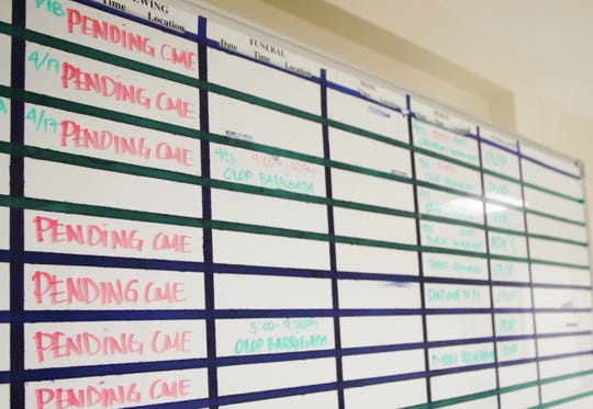 "A whiteboard at Our Lady of Peace Funeral Home helps staff with scheduling funeral services. ""Pending CME"" denotes which cases are still waiting to be examined by a clinical pathologist. Since the retirement of Guam's medical examiner, funeral services have been delayed."
