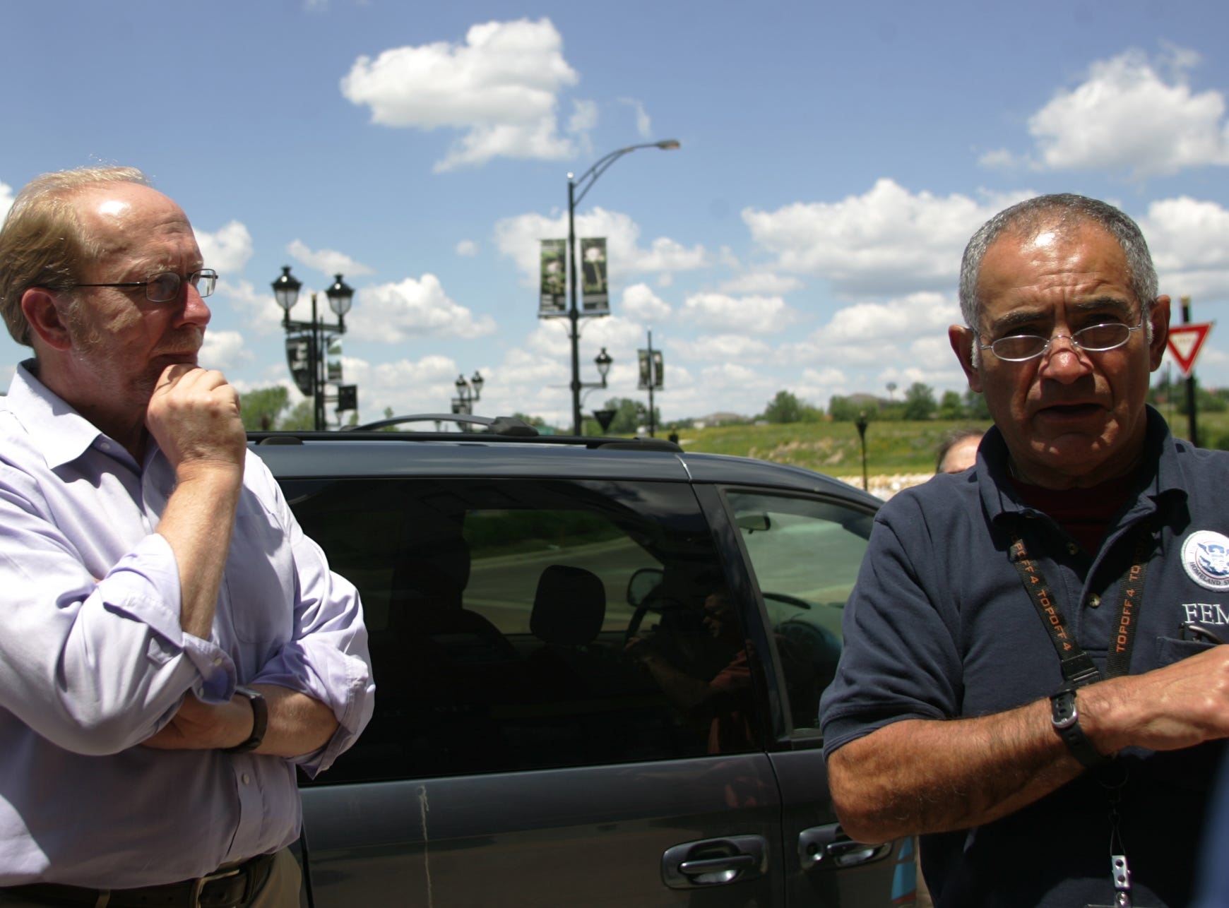 U.S. Rep. Dave Loebsack, left, listens as Ron Chaidez of the Federal Emergency Management Agency describes some of the post-flood cleanup work at the Iowa River Landing development in Coralville on Monday, June 30, 2008.