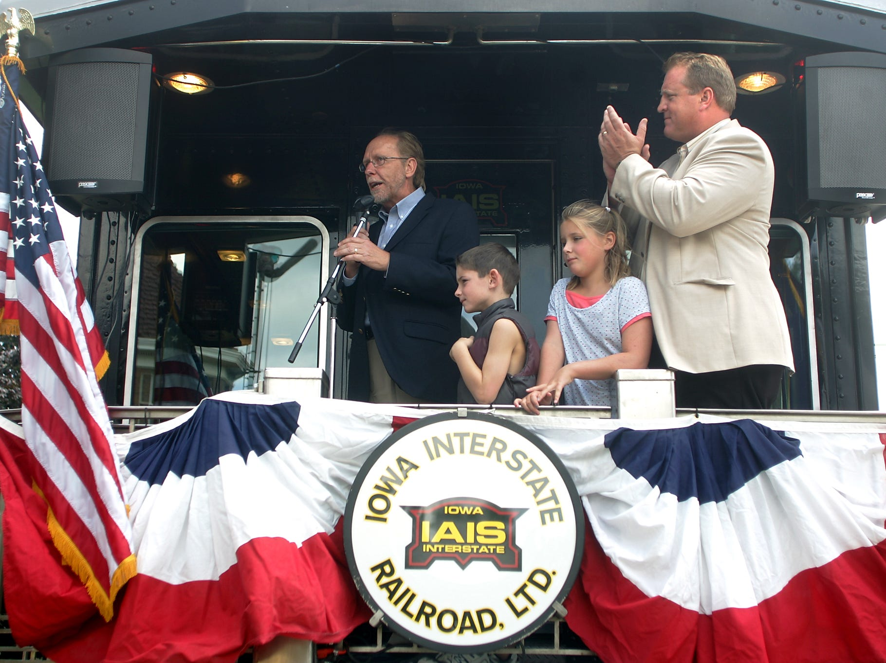 Iowa Gov. Chet Culver, right, claps as he and his children, John and Clare Culver, listen to U.S. Rep. Dave Loebsack (D-Iowa), left, speak at a stop in Iowa City, Iowa, during a train tour to promote plans for passenger rail service to Chicago on Sunday, July 26, 2009.