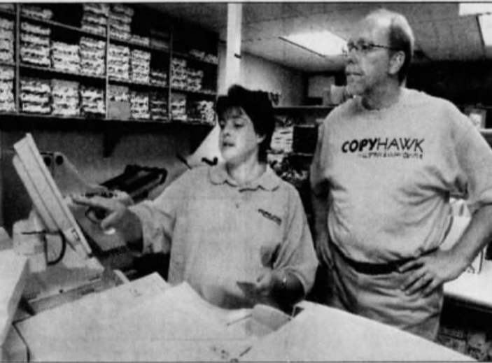 CopyHawk employee Tracy VandenBerg, left, shows Rep. Dave Loebsack how to use one of the center's copy machines Thursday, Aug. 23, 2007, at the CopyHawk center in the Iowa Memorial Union.