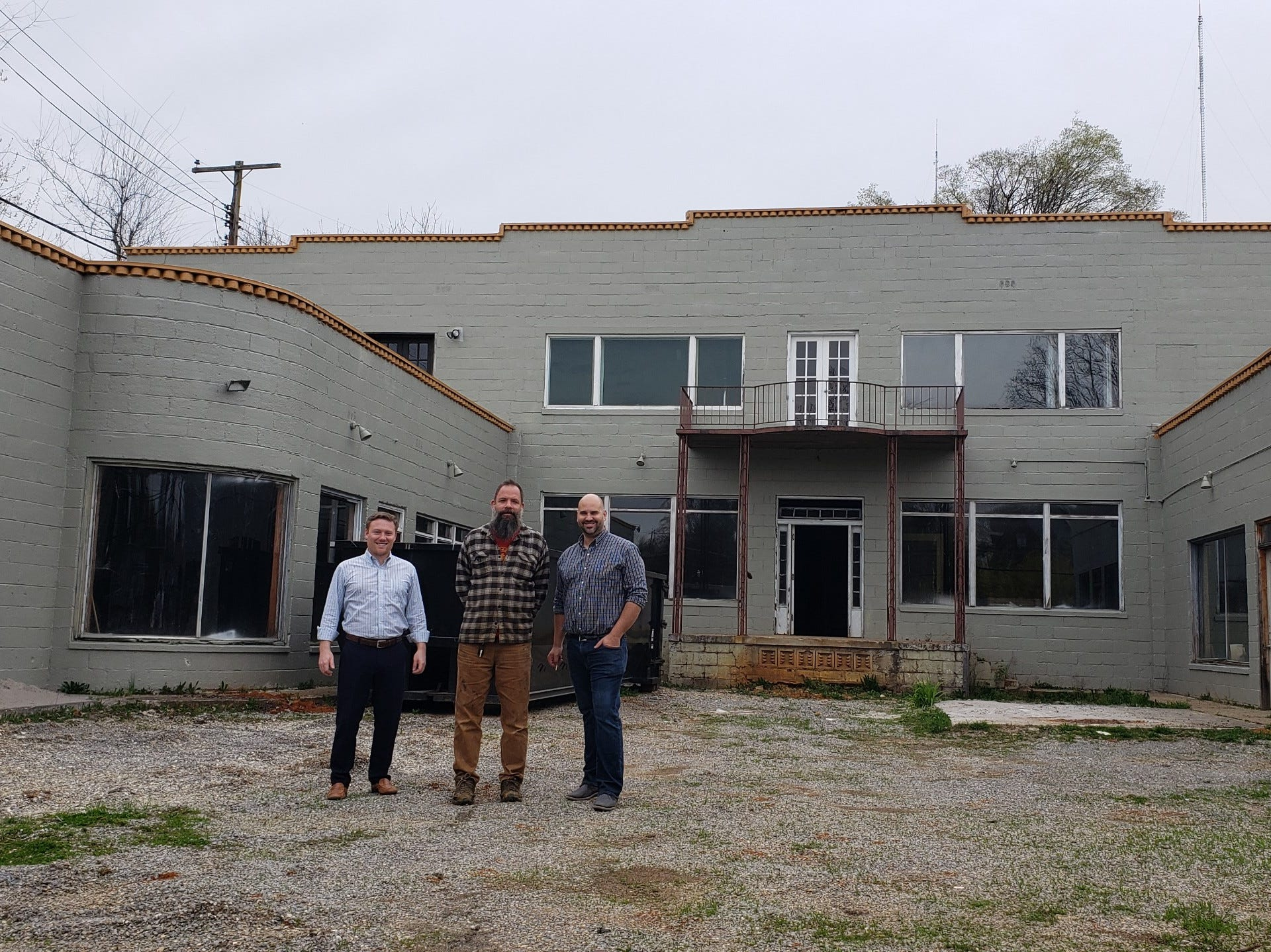 Tyler Fogarty, Jay McNabb and Luke Kendziorski, part owners of the Taggart Building on North Broadway, are shown in its courtyard.