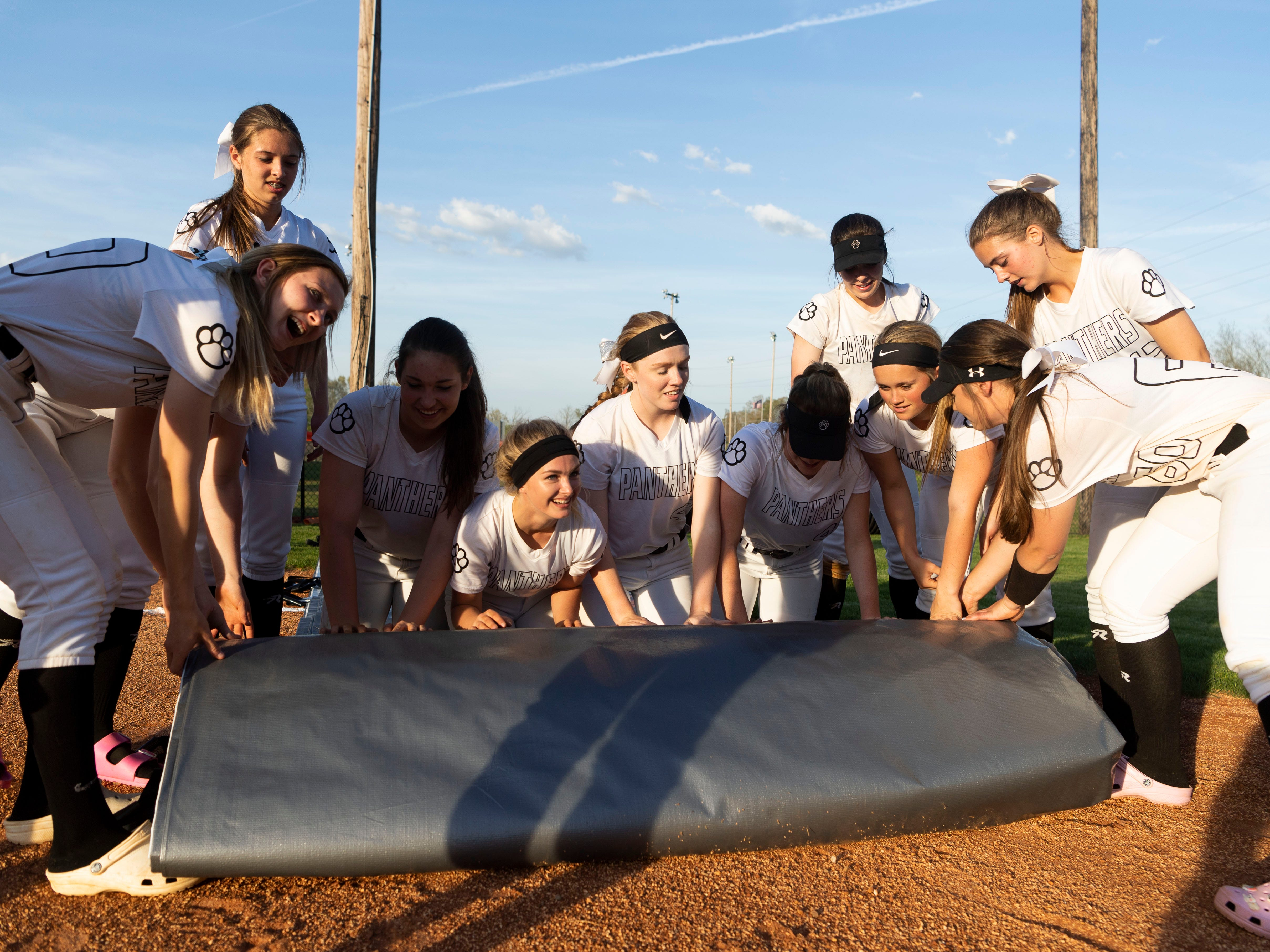 Powell players work together to unroll the tarp used to cover the infield after their game against Central on Thursday, April 11, 2019. It was the team's first game at home after rains destroyed the field earlier in the year.