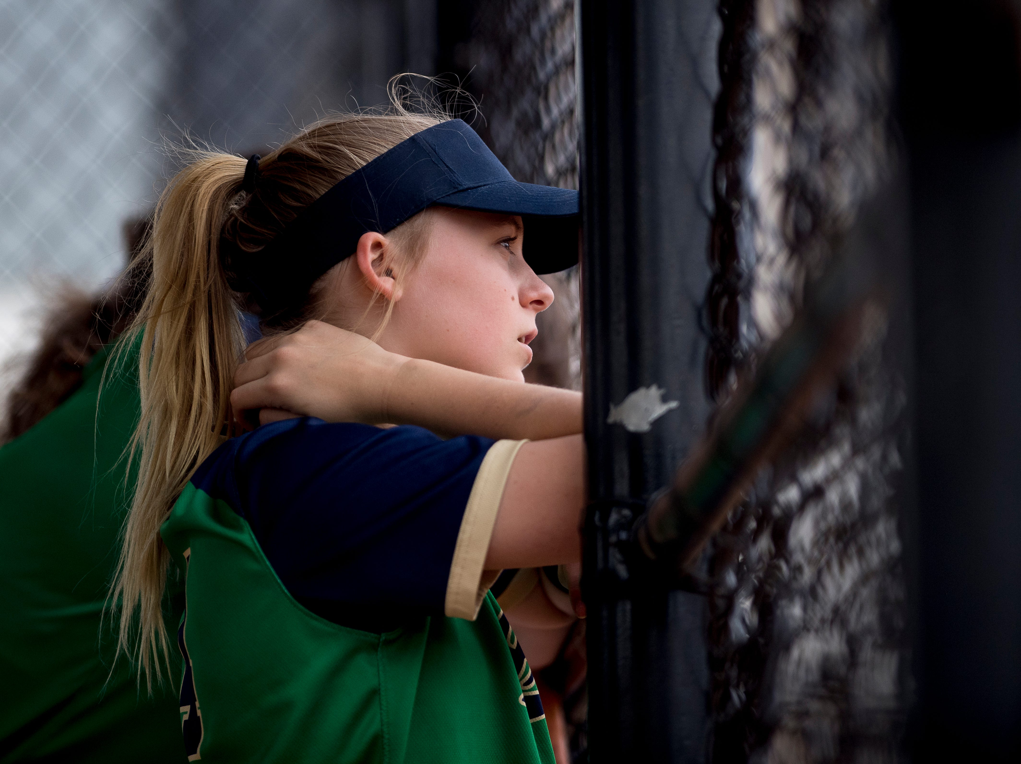 A Catholic player watches the game from the dugout during a softball game between Catholic and Karns at Caswell Park in Knoxville, Tennessee on Friday, April 12, 2019.