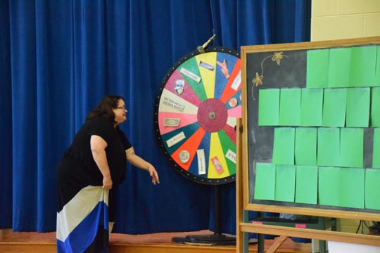 "Sheila Earl spins the wheel at the ""Wheel of Fortune"" game during her retirement assembly. April 9, 2019"
