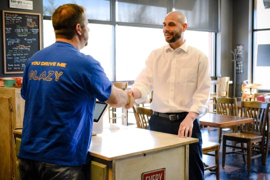 Rob Voigt agrees with Ryan Wells, left, of Beaver's Dough-Jo to pay $5 for the first 40 people to buy doughnuts at the shop Tuesday, March 5, 2019.
