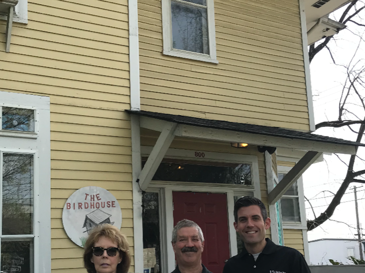 The Fourth and Gill Neighborhood Center – also known as the Birdhouse – will once again feature its original wraparound porch. Shown with rendering are Sue Russell, grant writer; Gordon Coker, who consulted on porch construction; and Brent Waugh, project lead and fundraising chair for the project.